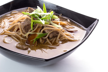 Thai soup with soba noodles and meal with chopsticks isolated