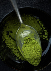 A bowl of matcha tea powder on a spoon