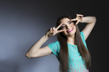 Smiling young woman looking through peace signs