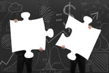 Two business people assembling blank white jigsaw puzzles with d