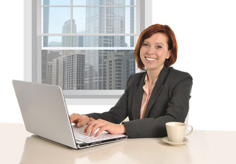 Happy successful business woman working at office computer