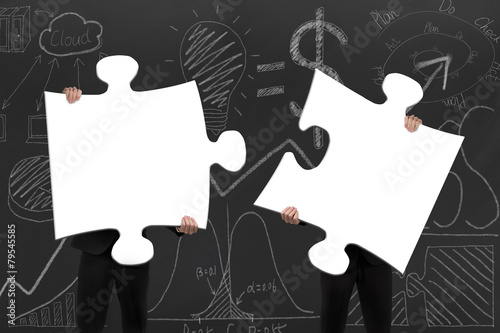 Two business people assembling blank white jigsaw puzzles with d - 79545585