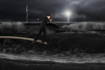 Businessman balancing on wooden board with dark stormy ocean
