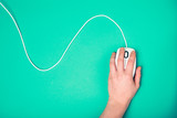 hand on computer mouse, emerald background