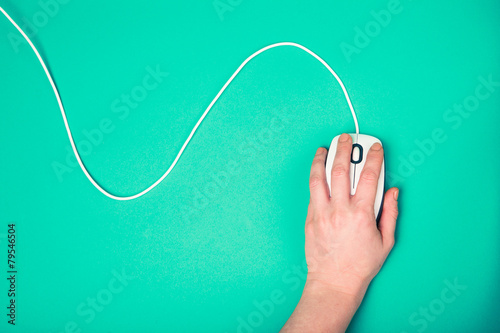 hand on computer mouse, emerald background - 79546504