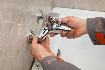 Plumber works in a bathroom replacing faucet, tap