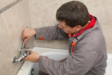 Plumber works in a bathroom replacing faucet, tap