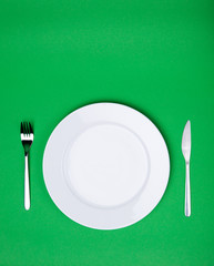 white plate, fork and knife on green background