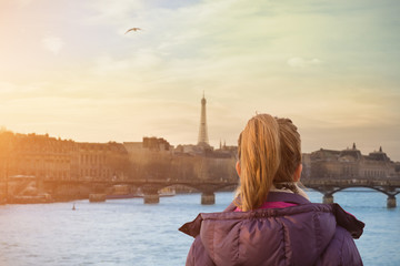 Lonesome girl watching at Paris city scape at sunset.