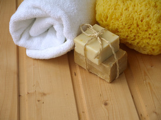 Towel,soap and sponge on the wooden background