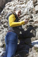 Girl climber using cellphone whilst climbing