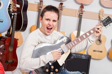 Man playing electric guitar on music shop
