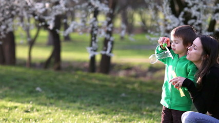 Two boys in the park, blowing and chasing soap bubbles