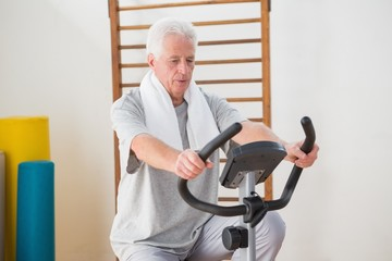 Senior man doing exercise bike
