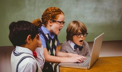 Shocked little school kids using laptop
