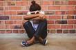 Leinwanddruck Bild - Tensed girl sitting against brick wall in school corridor