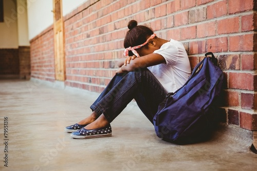 Wall Tensed girl sitting against brick wall in school corridor