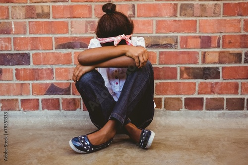 Tensed girl sitting against brick wall in school corridor - 79551333