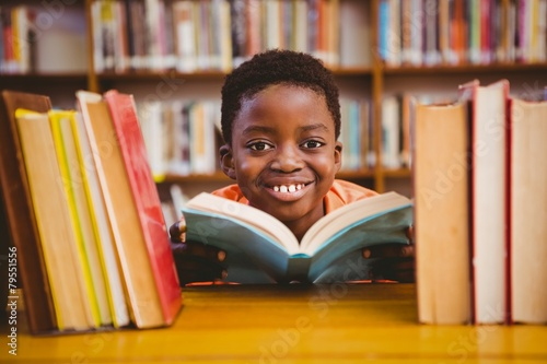Cute boy reading book in library - 79551556