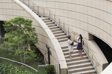 Two women on steps in Namba Park office and shopping complex.