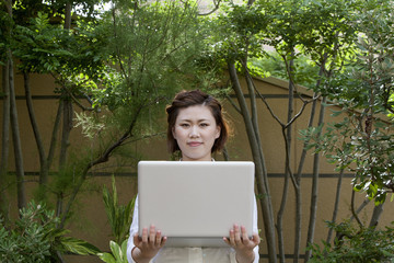 A woman holding a laptop in her arms and standing outdoors.