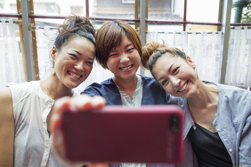 Three women looking at a cell phone, taking a selfie, sitting indoors.