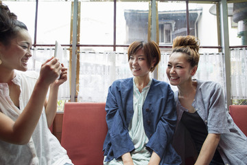 Three women sitting indoors, one holding a digital tablet, taking picture.