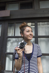 Woman standing outdoors, holding a camera.