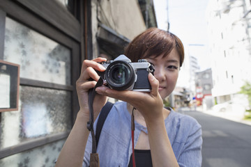 Woman standing outdoors, looking through a camera.