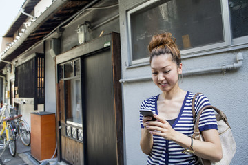 Woman standing outdoors, looking at cellphone.