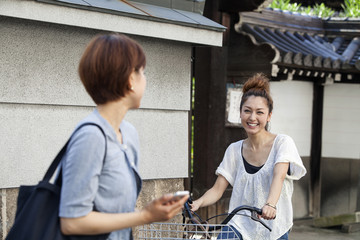 A woman chatting to another woman sitting on a bicycle.
