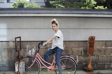A woman sitting on a pink bicycle.