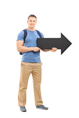 Young male student holding a big black arrow