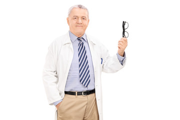Mature doctor holding a pair of glasses