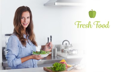 Fresh food against woman in the kitchen holding a salad bowl