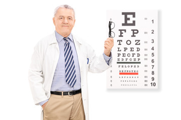 Optometrist holding glasses in front of eye chart