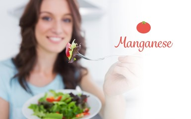 Manganese against brunette offering healthy salad
