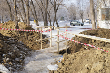 Freshly dug trench and temporary wooden bridge with fence