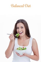 Balanced diet against smiling young woman eating a salad