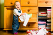 Domestic chores - baby throws out clothes - 79554334
