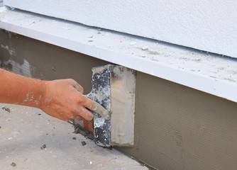 Man's hand plastering a wall with trowel.