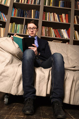 Old-fashioned Young man is sitting in a library and reading a bo