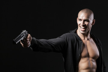evil smiling man shooting gun isolated on black background