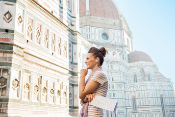 Happy young woman with map and audio guide in firenze