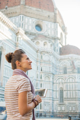 Happy woman with tablet pc in front of cattedrale in firenze