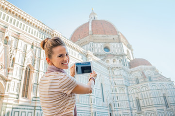 Happy woman taking photo with tablet pc of cattedrale in firenze