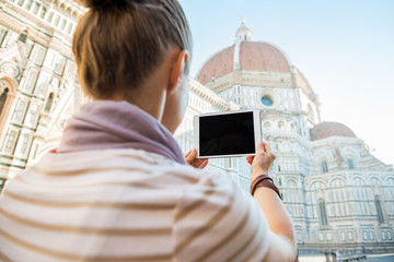 Young woman taking photo with tablet pc of cattedrale in firenze