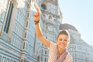 Happy young woman pointing in front of cattedrale in firenze