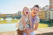 Smiling mother and baby girl standing on bridge in firenze