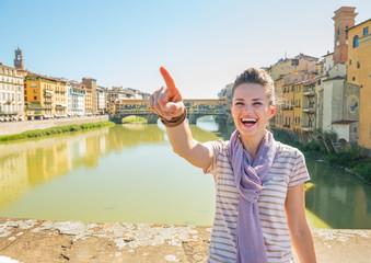 Woman standing on bridge overlooking ponte vecchio  in florence